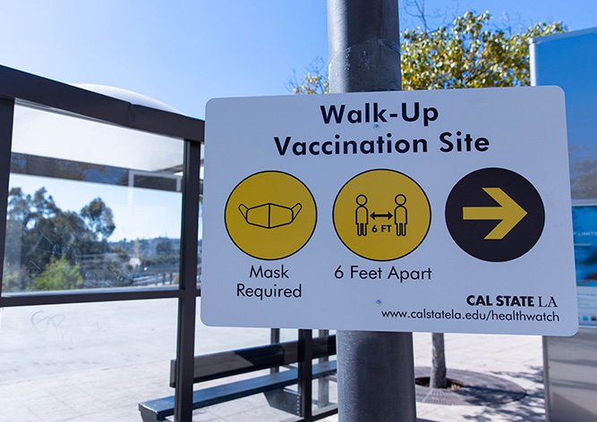 Sign stating 'Walk-Up Vaccination Site: Mask Required, 6 feet apart'