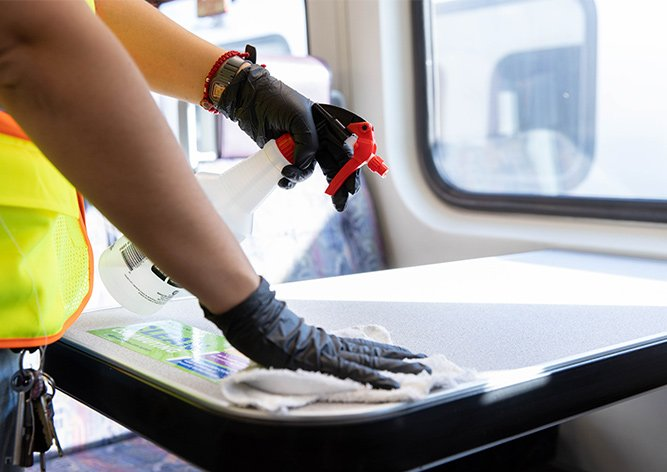 Metrolink employee spraying disinfectant on a table in a Metrolink train