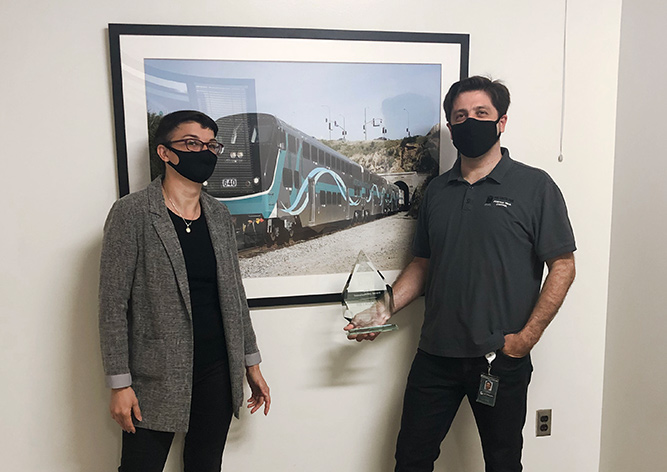Two employees posing with a framed photograph of a Metrolink train with a 2020 Sustainability Impact Award
