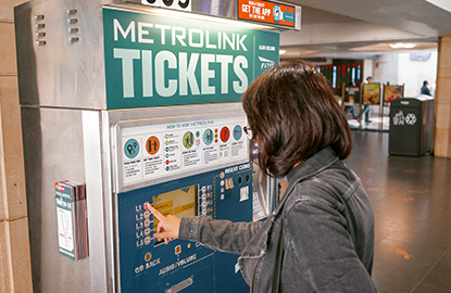 A woman buying a ticket from the Metrolink ticket machine
